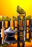 Tequila do ouro em um fundo reflexivo preto Fotografia de Stock