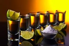 Tequila do ouro em um fundo reflexivo preto Fotografia de Stock Royalty Free