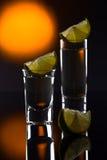 Tequila do ouro em um fundo reflexivo preto Foto de Stock