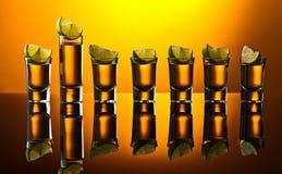 Tequila do ouro no fundo reflexivo Imagens de Stock