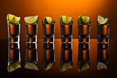 Tequila do ouro no fundo reflexivo Fotos de Stock