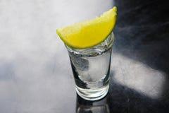 Tequila en vaso de medida con la cal Foto de archivo libre de regalías