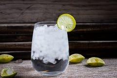 Tequila, GENIÈVRE, vodka dans un verre avec de la glace, chaux, une barre de cocktail image libre de droits