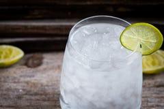 Tequila, GENIÈVRE, vodka dans un verre avec de la glace, chaux, une barre de cocktail photo libre de droits
