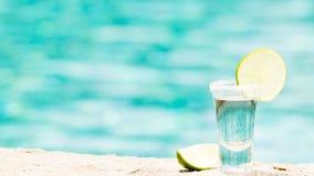 Tequila geschossen mit Kalk auf blauem Hintergrund lizenzfreie stockfotografie