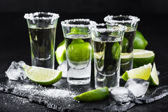 Tequila gold in short glasses with salt, lime slices. Mexican tequila gold in short glasses with salt, lime slices and ice on black background Royalty Free Stock Photography
