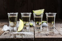 Tequila gold in short glasses with salt. Mexican tequila gold in short glasses with salt, lime slices and ice on a wooden table Royalty Free Stock Images