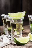 Tequila gold in short glasses with salt. Mexican tequila gold in short glasses with salt, lime slices and ice on a wooden table Stock Photography