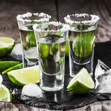 Tequila gold in short glasses with salt. Mexican tequila gold in short glasses with salt, lime slices and ice on a wooden table Stock Image