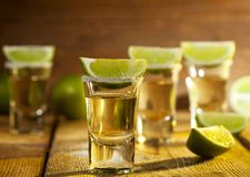 Tequila. Gold tequila shots with lime fruits on wooden background Stock Image