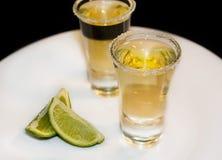 Tequila i små exponeringsglas med limefrukt arkivbilder