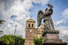 TEQUILA, JALISCO, MÉXICO - JULIO - 2015: Ángel en el primero plano con el behin de la iglesia del pueblo imagenes de archivo