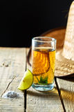 Tequila and lemon. Tequila with a lemon over a wood board Royalty Free Stock Photos