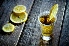 Tequila. And lemon on a wood background Royalty Free Stock Image