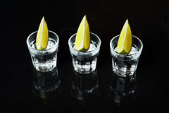Tequila with lime on black background Stock Images
