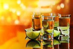 Tequila and lime. On a black glass table in bar Royalty Free Stock Image