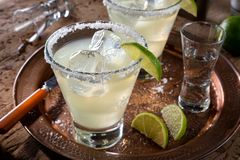 Tequila and Lime Margaritas. Delicious tequila and lime margaritas on a copper charger with coarse salt rimmer Royalty Free Stock Image