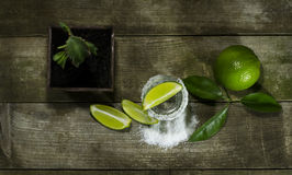 Tequila with lime and salt. On a wooden background stock image