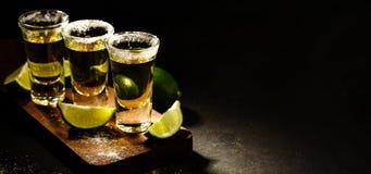 Tequila mexicano del oro con la cal y la sal en la tabla de madera Foto de archivo