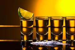 Tequila mexicano del oro en vidrios cortos con la cal imágenes de archivo libres de regalías