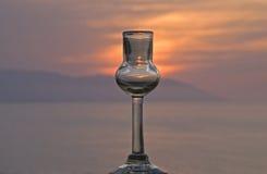Tequila ontsproten glas met zonsondergang een oceaanachtergrond Stock Foto