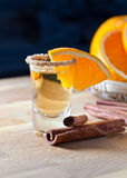 Tequila with orange and cinnamon. On a wooden table Royalty Free Stock Image