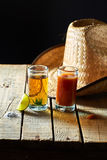 Tequila, sangrita and lemon. Tequila with a lemon and sangrita over a wood board Royalty Free Stock Photography