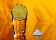 Tequila Shot. With a slice of lime in the glass and a pile of salt by the side on orange background (Selective Focus Royalty Free Stock Photos