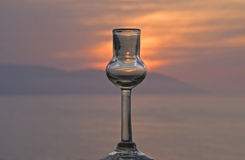 Tequila shot glass with sunset an ocean background Stock Photo