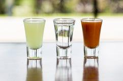 Tequila shot. Lemon and sangrita on a wood table stock image