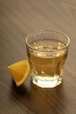 Tequila shot with lemon on a wooden table Stock Image