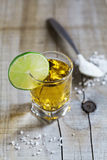 Tequila shot with lime and sea salt on rustic wooden board Stock Photos
