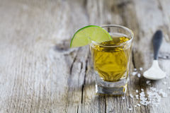 Tequila shot with lime and sea salt on rustic wooden board Royalty Free Stock Photo