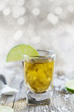 Tequila shot with lime and sea salt on rustic wooden board Stock Images