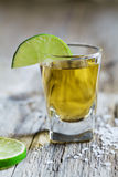Tequila shot with lime and sea salt on rustic wooden board Stock Photography
