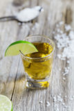 Tequila shot with lime and sea salt on rustic wooden board Royalty Free Stock Images