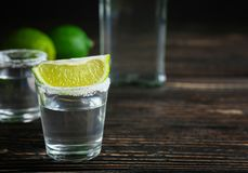 Tequila shot with lime slice and salt. On table stock image