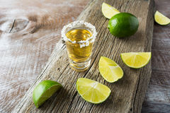 Tequila shot with lime slices on rustic wooden background Royalty Free Stock Photos