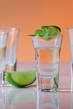 Tequila shot with a slice of lime on the glass orange background Royalty Free Stock Image