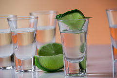 Tequila shot with a slice of lime on the glass orange background Stock Image