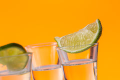 Tequila shot with a slice of lime on the glass orange background Royalty Free Stock Images