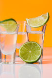 Tequila shot with a slice of lime on the glass orange background Royalty Free Stock Photography
