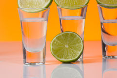 Tequila shot with a slice of lime on the glass orange background Stock Photos