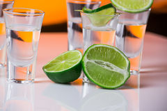 Tequila shot with a slice of lime on the glass orange background Stock Photography