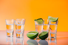 Tequila shot with a slice of lime on the glass orange background Stock Images