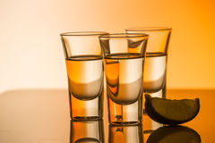 Tequila shot with a slice of lime on the glass orange background Royalty Free Stock Photos