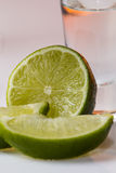 Tequila shot with a slice of lime on the glass orange background Royalty Free Stock Photo