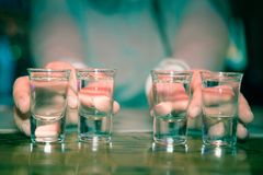 Tequila shots - alcohol. Bartender serving tequila shots with lemon Royalty Free Stock Image