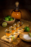 Tequila shots grouped together with a bottle and cut limes on a restaurant bar table. Golden Tequila shots with lime and salt served at mexican restaurant table Stock Images