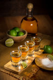 Tequila shots grouped together with a bottle and cut limes on a restaurant bar table Stock Photo